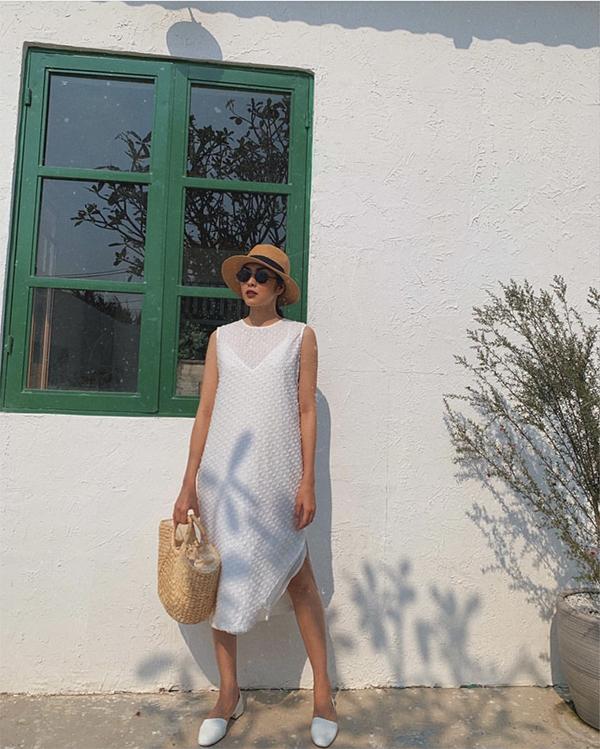 Tăng Thanh Hà dùng các phụ kiện thân thiện với môi trường như mũ nan, túi cói để mĩ cùng váy suông và giầy đế thấp tiệp sắc trắng.
