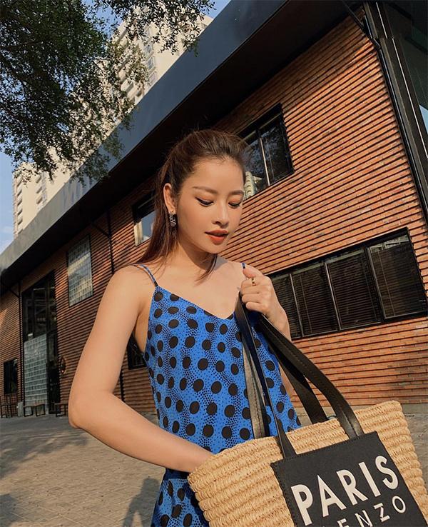 Vẫn là váy hai dây dáng suông nhưng Chi Pu lại chọn họa tiết chấm bi xanh đen để sử dụng. Phụ kiện đi kèm là túi cói đi kèm dây da đen.