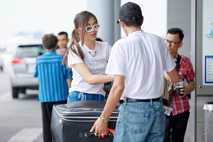 Á hậu Hoàn vũ giúp bố mẹ kiểm tra giấy tờ tùy thân trước khi vào sân bay làm thủ tục.