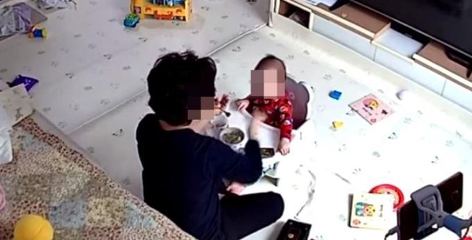 Bà Kim ép rồi tát vào mặt bé gái trong lúc cho ăn. Ảnh: Yonhap TV.