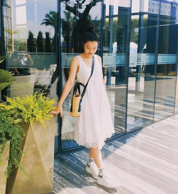 Đông Nhi nhẹ nhàng và đơn giản khi chọn váy suông mix cùng giầy thể thao. Ca sĩ chọn thêm túi cói để phối đồ street style.