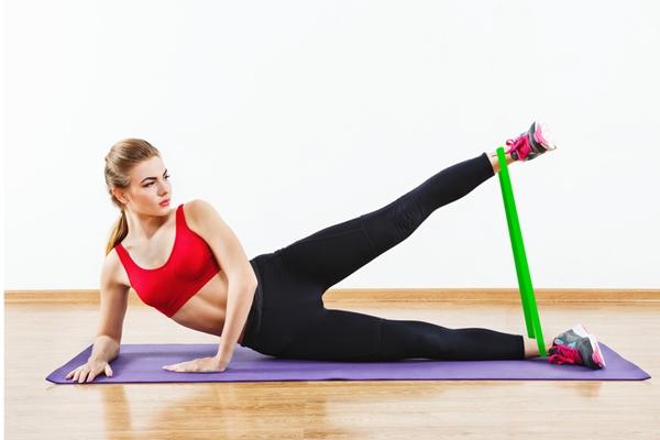Động tác đá chân ngang với dây đàn hồiTiếp tục sử dụng dây đàn hồi ở cổ chân, nằm nghiêng một bên, chân duỗi thẳng, đá cao một chân 10 lần rồi đổi bên.