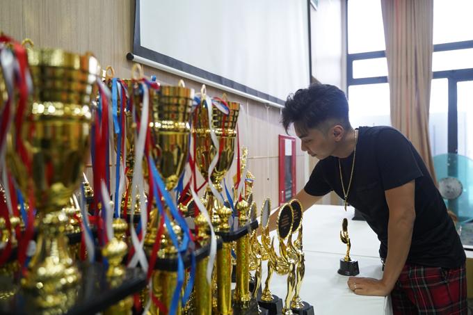 Trong khi đó ông xã của cô lại giúp vợ sắp xếp những chiếc cúp và tấm huy chương sẽ trao trong giải đấu.