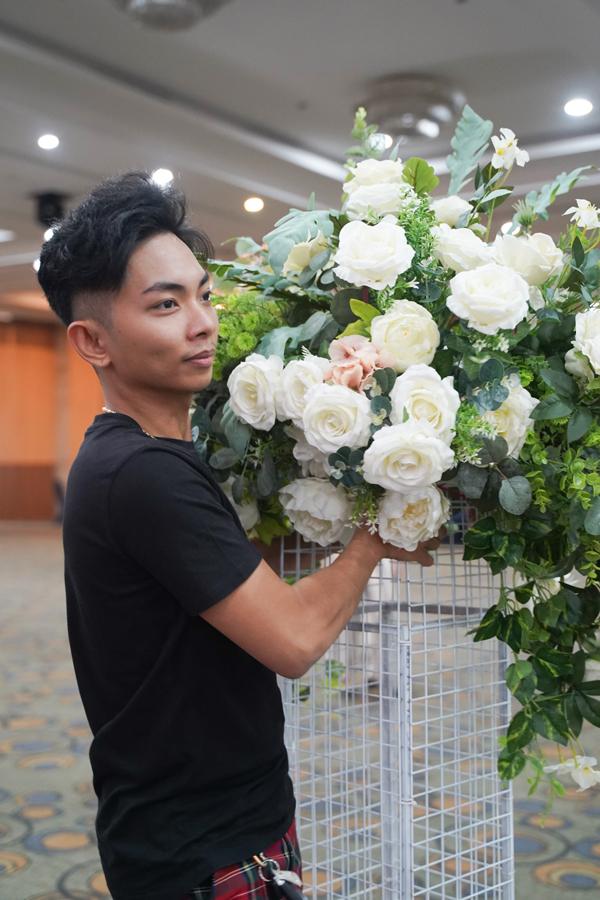 Anh không ngại bưng bê hoa để trang trí cho địa điểm thi đấu.