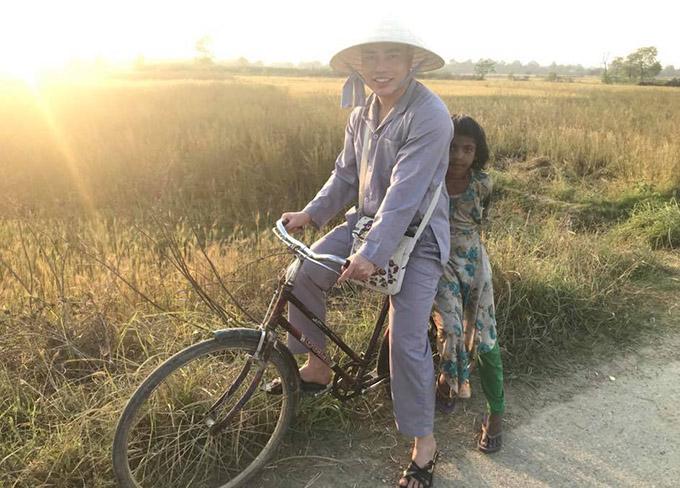 Chàng diễn viên chạy xe đạp chở một bé gái người Ấn đi chơi trên đường quê.