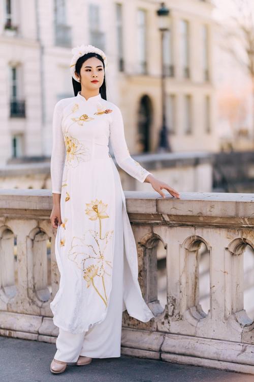 Diện áo dài trắng mang họa tiết hoa sen sẽ giúp bạn để lại ấn tượng sâu đậm với người xung quanh bởi vẻ dịu dàng và yêu kiều.