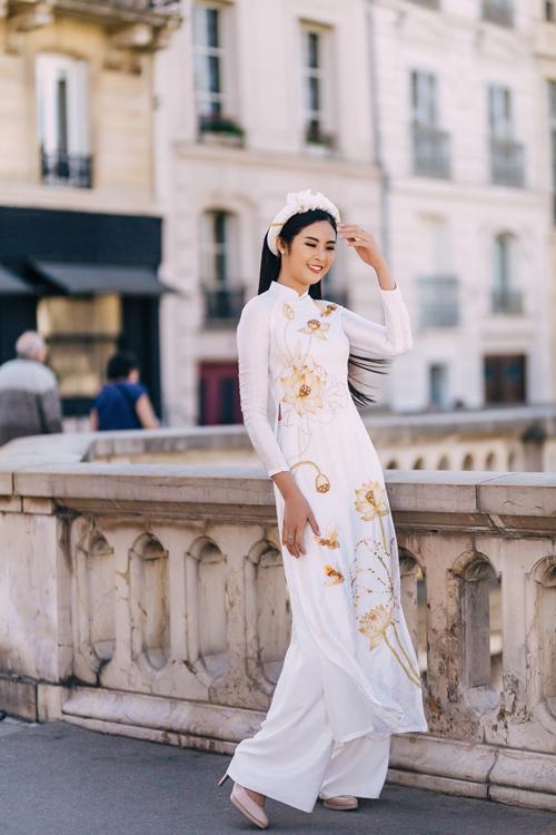 NTK - Hoa hậu Ngọc Hân sắp xếp họa tiết sen trải dài dọc thân theo đường chữ S giúp cô dâu trở nên cao ráo, nhấn vòng eo thon.