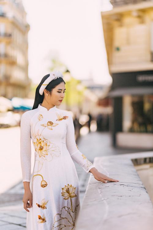 Không chỉ tôn nét thanh tân của người mặc, mẫu áo dài còn giữ được nét đẹp truyền thống thông qua phom dáng. Họa tiết mang gam vàng đồng giúp đem đến sự sang trọng, nổi bật cho tà áo.