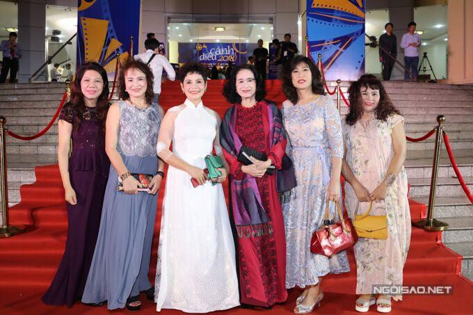 NSND Tràn Giang (áo dài đỏ) và NSND Minh Châu (áo dài trắng) chụp hình cùng các đồng nghiệp.