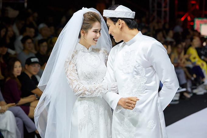 Diện áo dài ren trắng, Ngọc Trinh diễn ăn ý cùng chú rể Thuận Nguyễn. Cả hai trao nhau ánh mắt tình tứ khi catwalk.