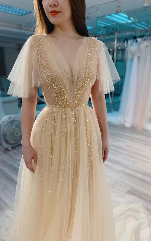 MC xinh đẹp phải lòng một thiết kế trong bộ sưu tập mới của Phương Linh, màu nude đính pha lê và đá màu ánh vàng đồng. Chiếc váy nguyên gốc có dáng chữ A xòe nhẹ và không tay. Tuy nhiên, để phù hợp với tính trang trọng của một lễ trao giải, NTK đã làm mới mẫu váy bằng chi tiết tay áo cánh tiên. Đây cũng là một mẹo hay dành cho các cô dâu nếu muốn tăng thêm sự kín đáo, thanh lịch trong ngày đại hỷ.