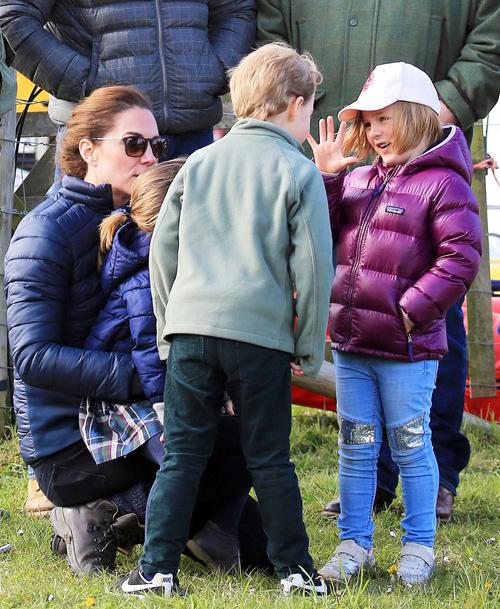 Hoàng tử George diện áo khoác kaki xanh, quần jeans tối màu, đi giày thể thao đen trắng khỏe khắn của nhãn hiệu Nike. Trong khi đó, Mia mặc áo phao tím, quần bò sequin lấp lánh ở đầu gối và đội mũ lưỡi trai. Công chúa Charlotte ngồi ngoan trong vòng tay mẹ khi hai anh chị trêu đùa nhau.