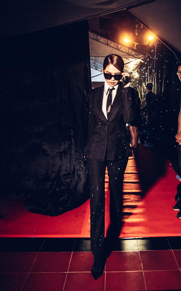 Ngọc Trinh khiến nhiều khán giả bất ngờ và thích thú với cách xây dựng hình ảnh hoàn toàn mới lạ. Tạm rời xa các mẫu váy sexy, người đẹp chọn suit và các phụ kiện tiệp sắc đen để xây dựng phong cách chuẩn men.Phong cách thảm đỏ của Ngọc Trinh được lấy cảm hứng từhình tượng nhà thiết kế Karl Lagerfeld - huyền thoại của thương hiệu Chanel.
