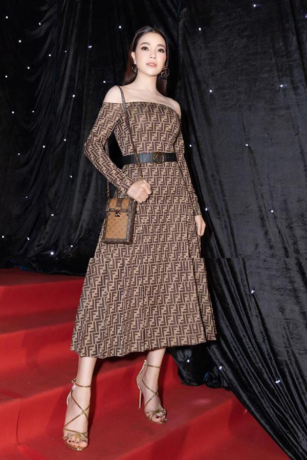 Trà Ngọc Hằng khoe vai trần gợi cảm cùng váy Fendi. Phụ kiện sandal màu vàng gold và túi Louis Vuitton được người đẹp chọn lựa để hoàn thiện set đồ.
