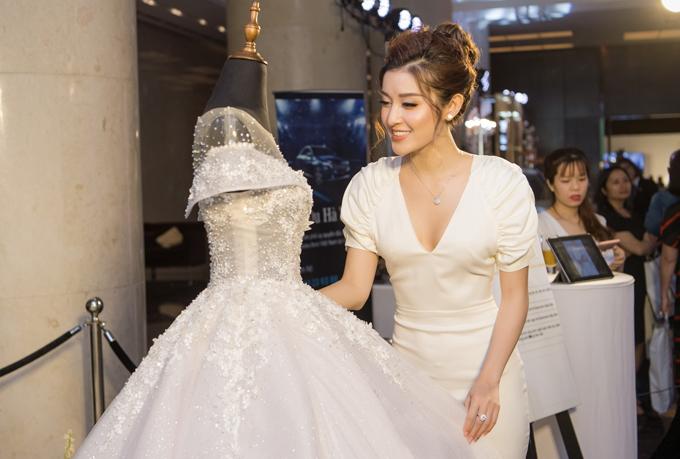 Á hậu diện váy trắng bó sát với phần cổkhoét sâu lấp ló vòng 1 gợi cảm. Để ngoại hình thêm phần yêu kiều, cô mix cá phụ kiện trang sức ngọc trai cùng set đồ.