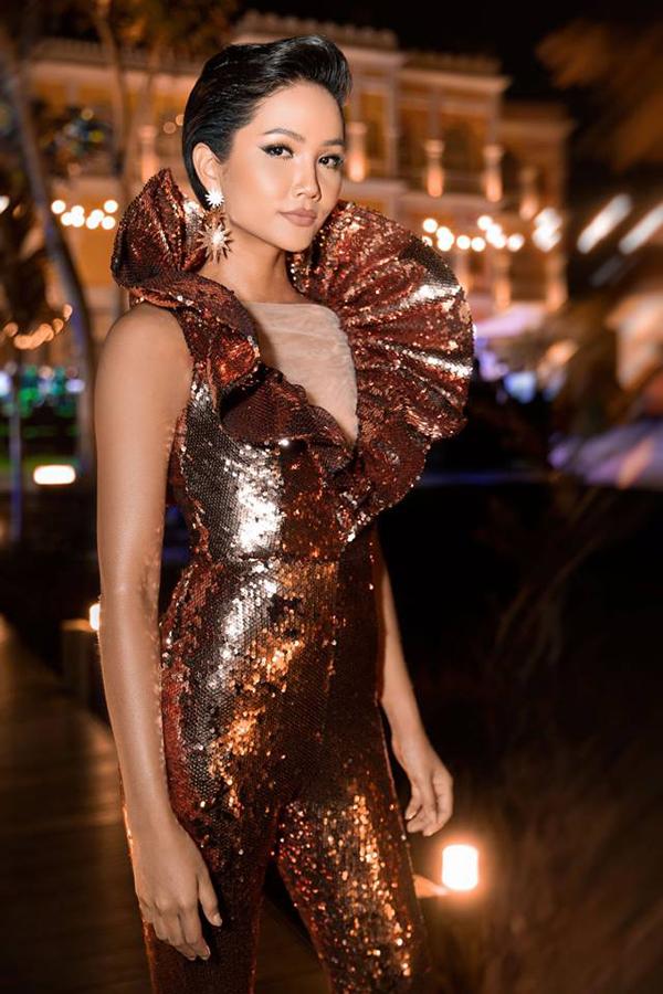 Ngoài việc sử dụng chất liệu sequins màu vàng gold, nhà thiết kế Kim Khanh còn giúp bộ jumpsuit của HHen Niê thêm ấn tượng nhờ phần cổ bèo nhún to bản.