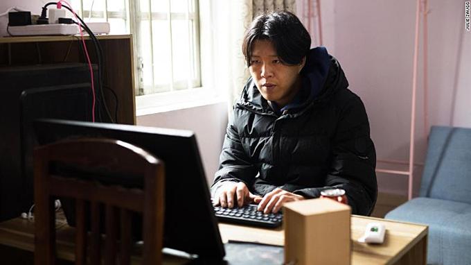 Wu Nengji dựng phim trước màn hình máy tính đã mất chân, phải tựa vào ghế. Ảnh:CNN.