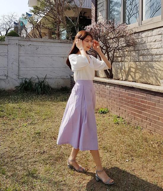 Chân váy midi màu tím khoai môn nhạt mang tới điểm nhấn vừa đủ về màu sắc khi kết hợp cùng blouse trắng.