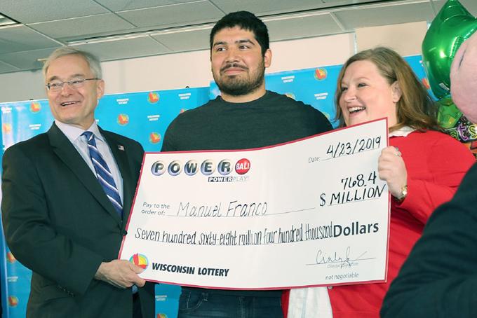 Người trúng giải độc đắc Manuel Franco (giữa) và hai đại diện của công ty xổ sốWisconsin. Ảnh: CNBC.