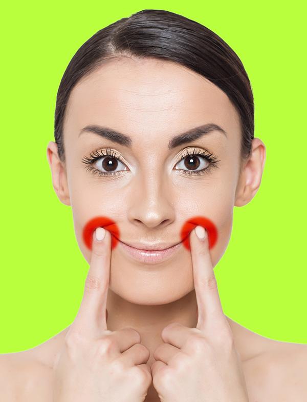 Mìm cười, đặt hai ngón tay trỏ lên điểm trên cùng của khoé môi, đẩy da lên cao để hạn chế nếp nhăn, cải thiện tình trạng da chảy xệ.