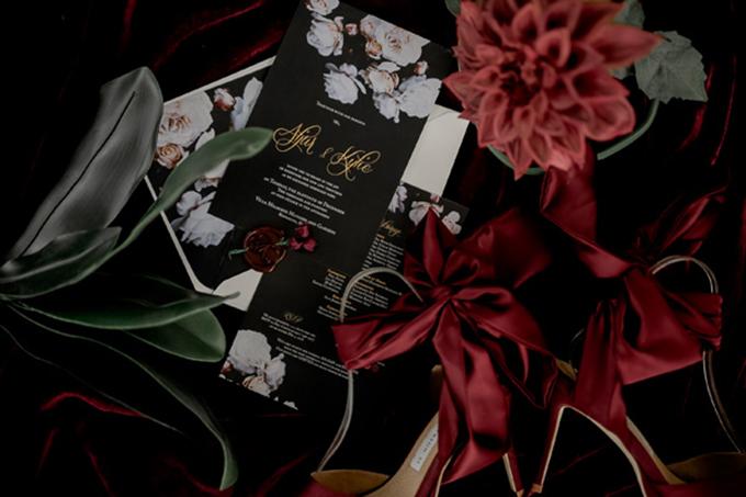 Bộ thiệp cưới hướng đến sự sang trọng với tông màu đen, đỏ mận và vàng đồng. Uyên ương niêm thiệp bởi con dấu sáp và một bông hoa lụa màu đỏ sẫm.