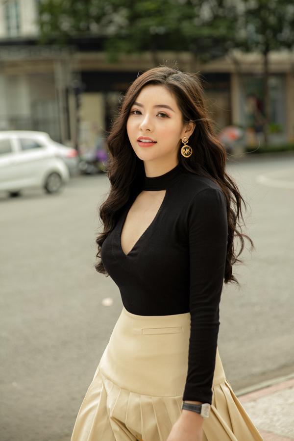 Chân váy xòe tông màu trung tính được tạo điểm nhấn bằng những nếp gấp tinh tế. Trang phục đi kèm là áo thun ôm với chi tiết cut-out phần ngực áo.