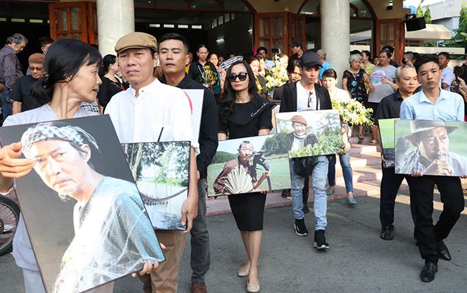 Các đàn em mỗi người ôm một bức ảnh chụp những vai diễn để đời của Lê Bình tới nghĩa trang. Khi còn sống, nam diễn viên hay được giao đóng những vai người nông dân nghèo khổ.