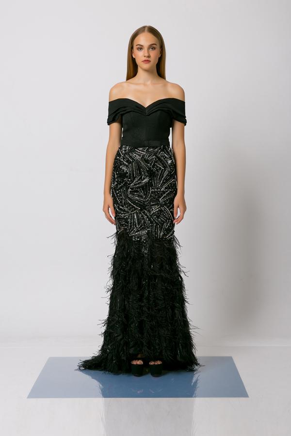 Váy dạ hội trễ vai được tạo thêm điểm nhấn bằng lông vũ, họa tiết sequins đính kết thủ công.