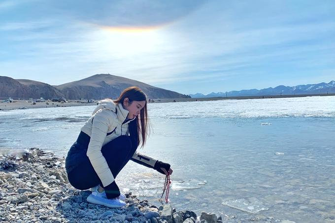 Vừa ngắm nhìn hào quang trên trời, Huỳnh Vy nhúng các vật phẩm thỉnh được trước đó xuống hồ để cầu bình an, may mắn.