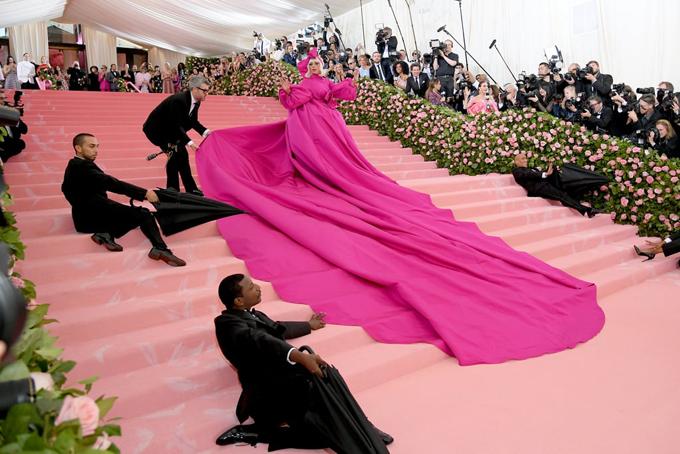 Gaga tung váy, khoe bộ đầm hồng của nhà thiết kế Brandon Maxwell trải dài gần hết bậc cầu thang.