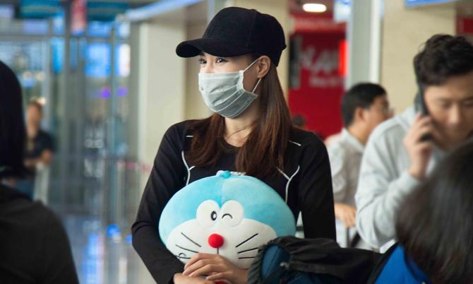 Lan Ngọc bịt khẩu trang, ôm mèo bông ở sân bay