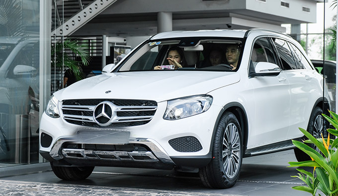 Nam ca sĩ lái xe chở vợ ra về sau khi hoàn tất các thủ tục bàn giao, nhận xe mới.