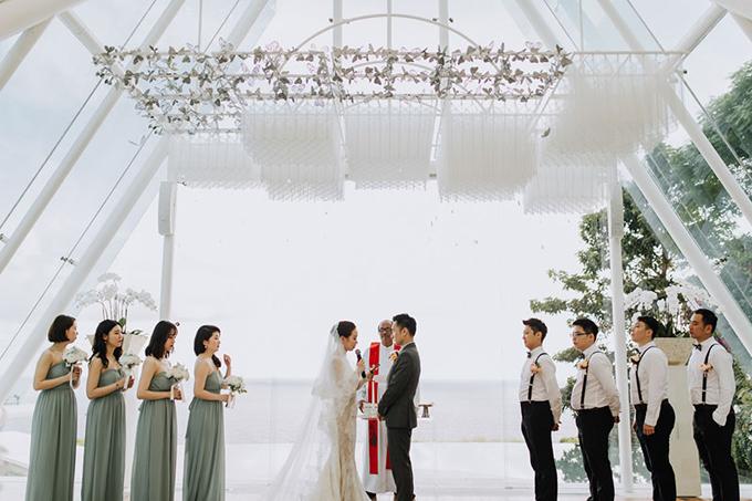 Phía trên trần nhà được tô điểm bởi những cánh bướm 3D, tạo sự lãng mạn. Dàn phù dâu diện bộ suit màu xám - xanh ngọc bích còn phù rể diện áo sơ mi, quần âu và dây đai quần.