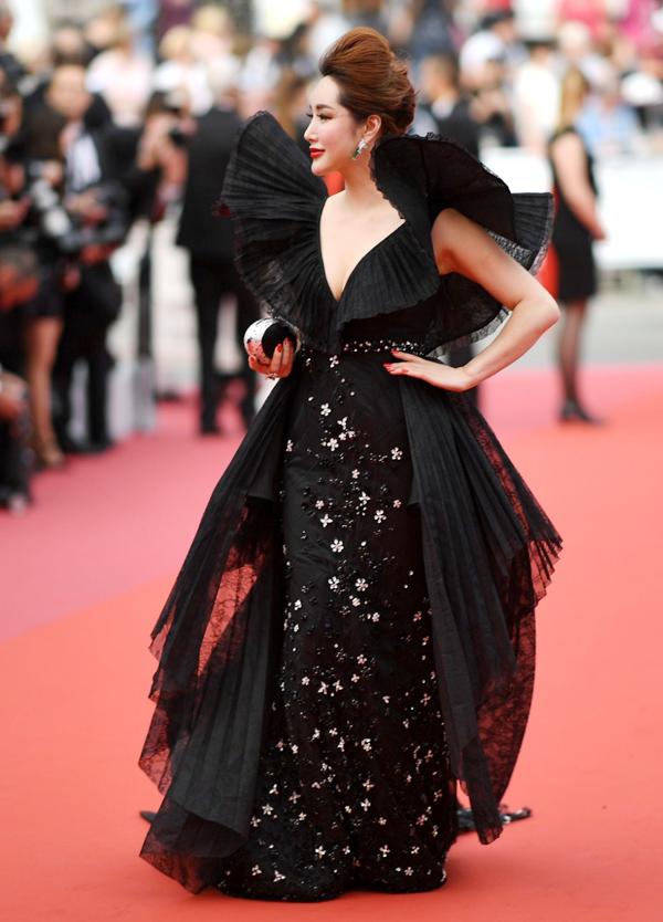 Phần vải dập ly kích thước lớn khiến bộ váy đen thêm nặng nề, rườm rà.