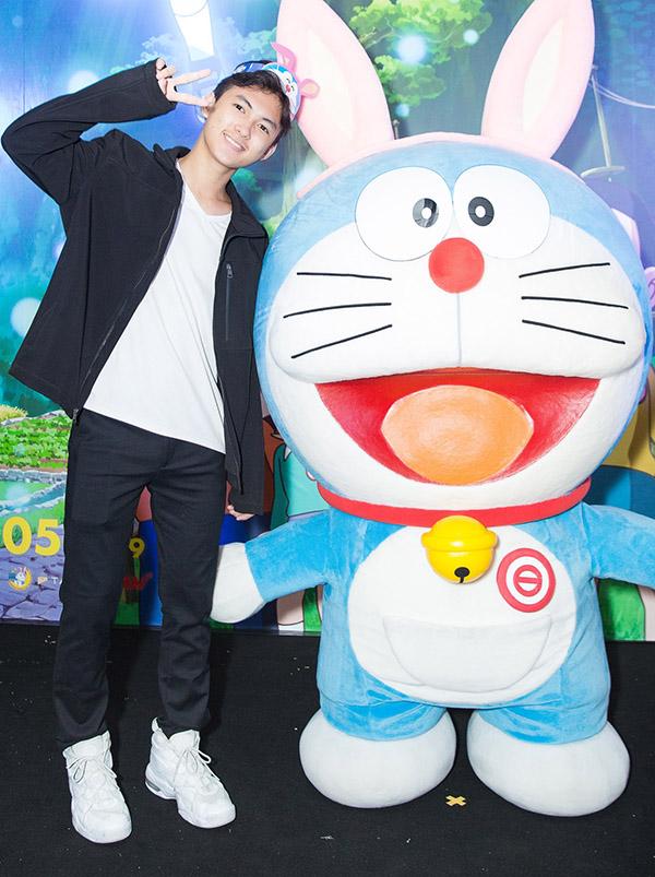 Sao nhí Thịnh Vinh tạo dáng xì tin bên mèo máy Doraemon bằng bông.