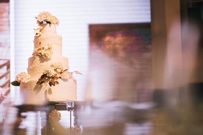 Bánh cưới của cô dâu chú rể được trang trí với hoa văn ren và các bông hoa.