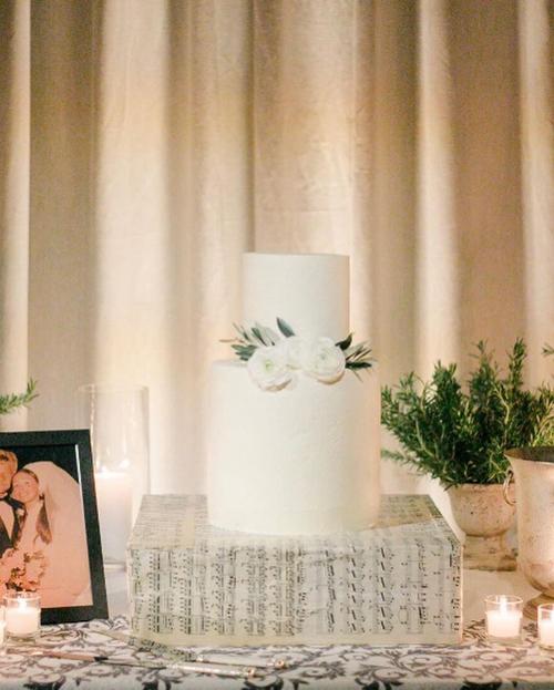 Bánh cưới của uyên ương được đặt trên đế hình khuông nhạc, mang phong cách tối giản khi không có hoa văn mà chỉ có rất ít hoa tươi trang trí.