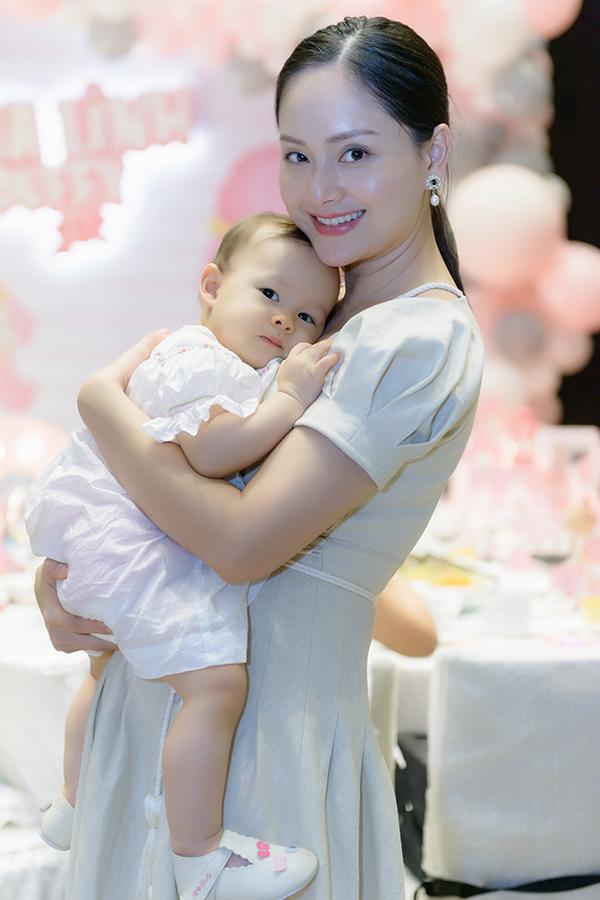 Bé Lina Linh tựa đầu vào mẹ trong bữa tiệc. Mỗi khi được mẹ đăng hình ảnh trên Facebook, cô bé đều nhận được nhiều lời khen bởi vẻ xinh xắn, đáng yêu và lanh lợi.