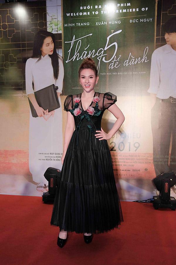 Nữ ca sĩ mặc váy voan đen dài kết hợp giầy cao gót đen, vô tưtạo dáng tại sự kiện.