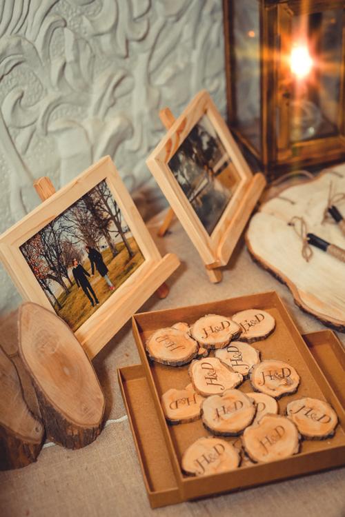 Bàn gallery có ảnh cưới và những miếng gỗ được khắc tên của hai vợ chồng.