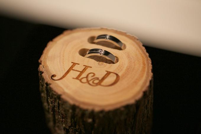 Cận cảnh cặp nhẫn cưới của đôi vợ chồng được đặt trên một khúc gỗ.