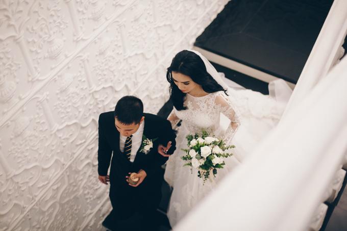 Trong ngày trọng đại, cô dâu Kiều Diễm diện váy cưới từ NTK Vincent Đoàn - người am hiểu cá tính và phong cách thời trang của cô. Tôi nói với NTK rằng muốn mặc một bộ váy cưới phù hợp với không gian, buổi lễ theo nghi thức tôn giáo. Khi nhận bản phác thảo, tôi đã ưng ý từ cái nhìn đầu tiên. Váy cưới của cô dâu được làm từ chất liệu voan, họa tiết thêu tay kết hợp lông vũ mang đến sự mềm mại, tôn vẻ đẹp tinh khôi của cô dâu.