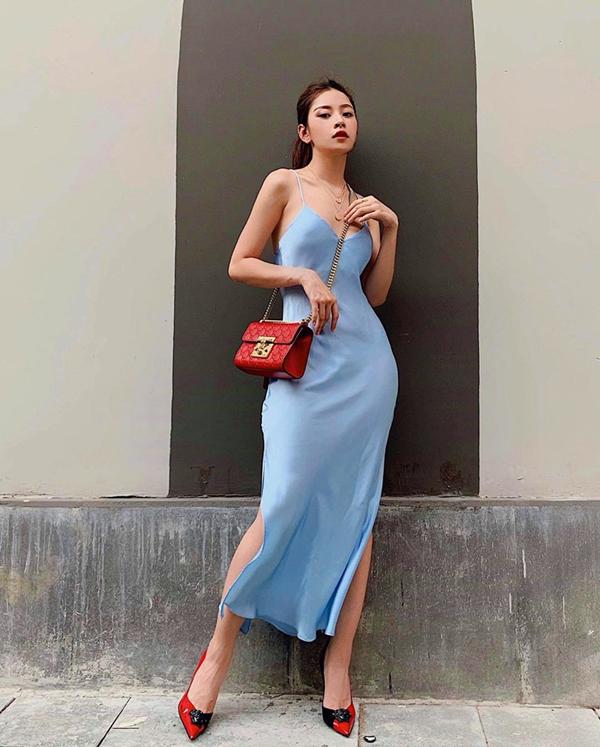 Chi Pu giúp mình có được nét mong manh, dịu dàng khi chọn váy lụa kiểu hai dây và đi kèm đường xẻ cao. Phụ kiện đồng điệu sắc màu được ca sĩ lựa chọn để tạo điểm nhấn cho tổng thể.