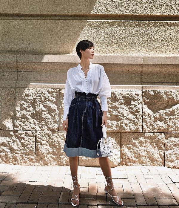 Chân váy denim cũng là sản phẩm lên ngôi ở mùa hè 2019. Khánh Linh The Face giúp mình cá tính hơn khi phối chân váy lưng cao cùng sơ mi trắng, sandal cao gót và túi Fendi.