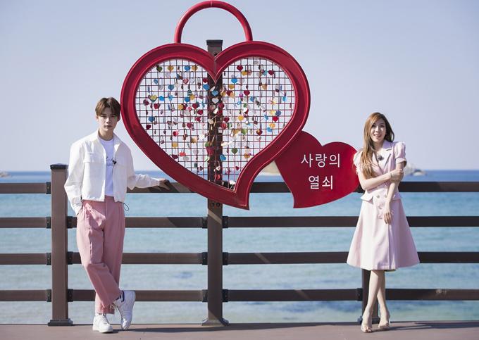 Hai ca sĩ mặc ton-sur-ton hồng rủ nhau đi tham quan các địa danh đẹp ở xứ kim chi.