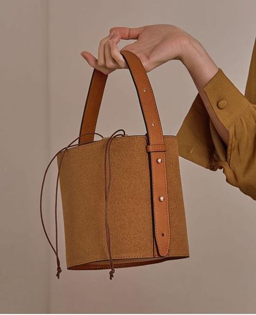 Túi trống, túi rút dây, túi dáng cà men cũng được thể hiện một cách ấn tượng trên nguyên liệu vải bố và da bò.