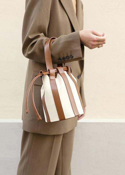 Bucket bag độc đáo nhờ được phối hợp hai chất liệu vải canvas và da nâu.Dáng túi cỡ trung nhỏ gọn phù hợp với việc mix đồ street style và đi làm.