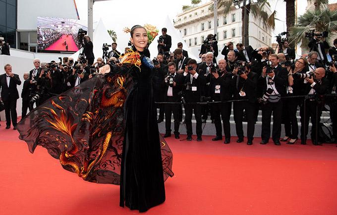 Trái ngược với phong cách phóng khoáng của các mỹ nhân đồng hương, Trương Thị May chọn áo dài nhung đen sang trọng kèm áo choàng hình rồng nổi bật, khẳng định dấu ấn Việt Nam ở Cannes.