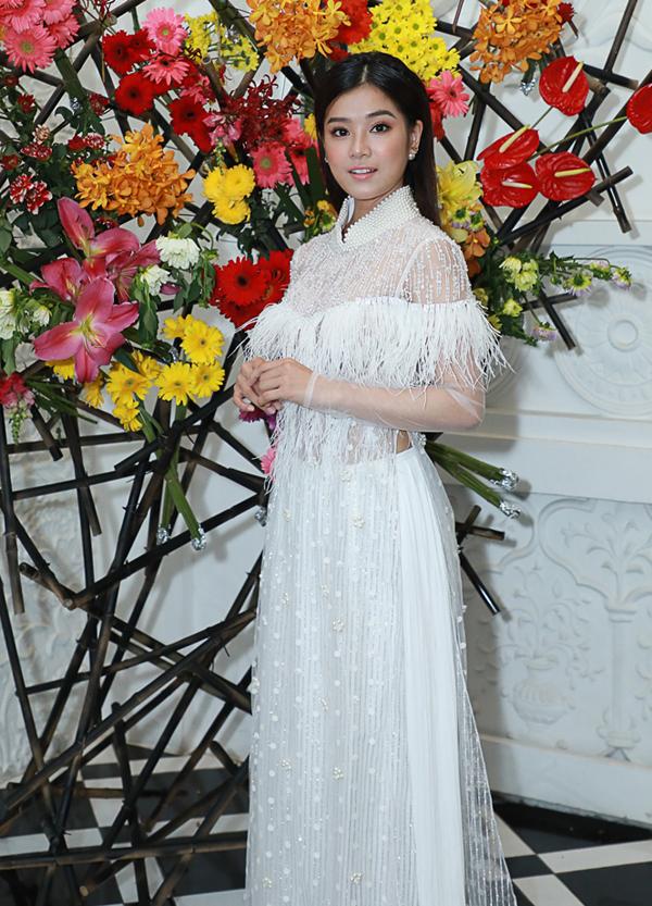 Ca sĩ Hoàng Yến Chibi điệu đà trong tà áo dài đính lông vũ.
