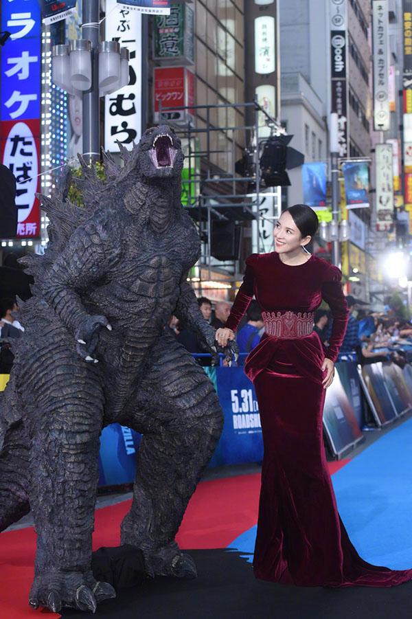 Chương Tử Di vui vẻ tạo dáng cùng mô hình Godzilla. Quái vật này xuất xứ từ Nhật Bản, nên bộ phim càng được chào đón ở xứ sở mặt trời mọc.